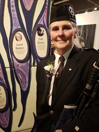 Gail Brown stands next to the 'arts' pillar, displaying female trailblazers at the unveiling of 100 Years 100 Women.