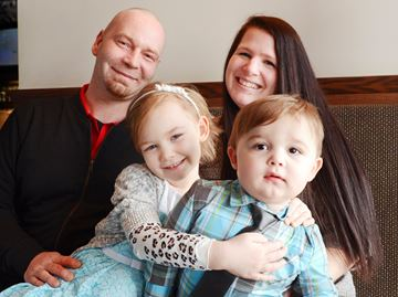 Arianna Koeniger hugs her little brother Alexander while dad Daniel and mom Shelley Duncan look on at Boston Pizza, where a fundraiser was held in Arianna's honour. Arianna lives with acute lymphoblastic leukemia.