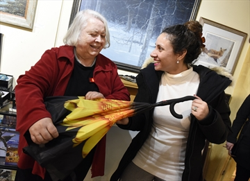 Christina Chiapetta (right) shows Hedi Nowak, owner of The Upstairs Gallery, the yellow umbrella she bought at the first Cash Mob Milton.