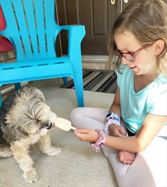 Aliyah Brito feeds Charlie one of her home-made pupsicles, which are available for sale this summer.