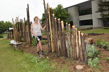 Sherry Saevil one of the co-founders of the Grandmother's Voice stands in the now completed Indigenous healing and medicine garden alongside the cedar poles that came from Crawford Lake Conservation Area, where they once stood as a palisade around the reconstructed 15th century longhouse village.